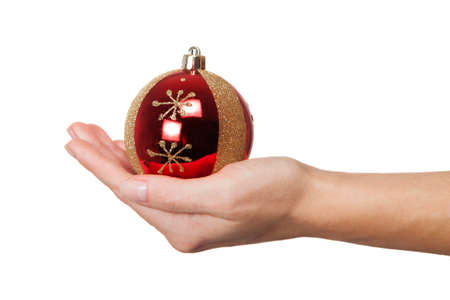 Hand holding red christmas tree ball isolated on white