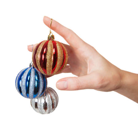 Hand holding three different colored christmas tree balls