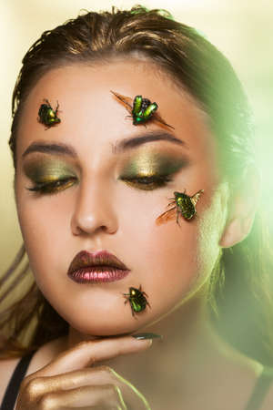 Portrait of a young woman with beetles golden bronze on her face