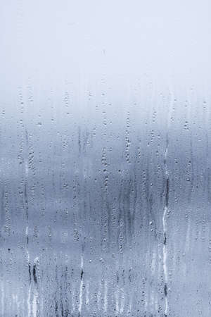 Raindrops on window glass. Abstract background. Blue tone