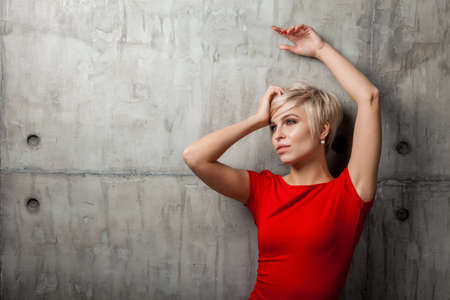 Blonde woman with a short haircut in a red dress against the background of the old wall