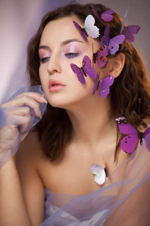 Beautiful young woman with artificial butterfly in curly hair.