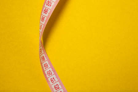 White measuring tape with red marks on yellow background