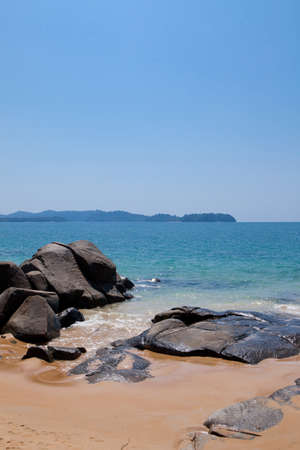 Sandy beach with huge stones against the blue sea on a sunny day in Thailand.