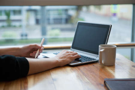 Hands using laptop and notebook with cup of tea on wooden table in cafe. A man works remotely using a laptop while sitting in a cafe.