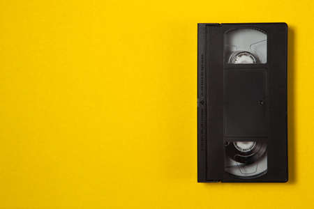 Video cassette videotape on a yellow background. Top view with place for text. Save your memories on modern media.