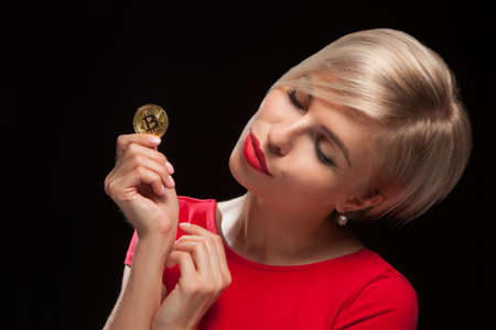 Woman holding physical bitcoin cryptocurrency coins in her hands. Stock Photo