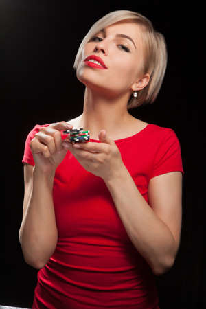 Beautiful blond woman showing gambling chips on black background.