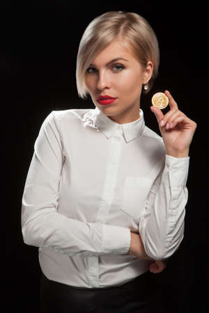 Woman holding physical bitcoin cryptocurrency coin in her hand.