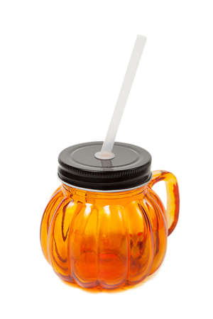 Glass empty jar. Orange mug with a black cover, handle and straw isolated on white background.