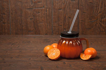 Glass jar of fresh orange juice with slice of tangerine or mandarin orange fruit on old wooden table. Orange mug with a black cover, handle and straw with tangerines.