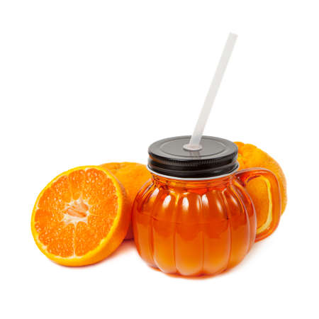 Glass jar of fresh orange juice with slice of tangerine or mandarin orange fruit isolated on white background. Orange mug with a black cover, handle and straw with tangerines. Stock Photo