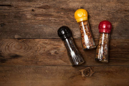 Two mills with spices for meat on an old wooden table. Top view. Free space for your text. Stock Photo