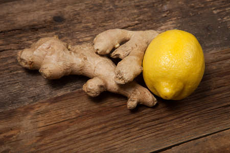 Close up of fresh ginger root spice and lemon on old wooden table Stock Photo
