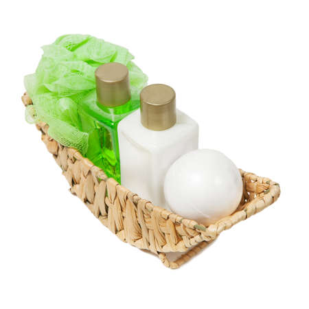 Body care cosmetics, sea salt, body lotion, shower gel, washcloth in a wicker basket on neutral background. Stock Photo