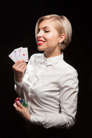 Beautiful blond woman showing a poker cards and gambling chips on black background Stock Photo