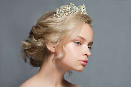 Beautiful blond woman in the image of a bride with a tiara in her hair.