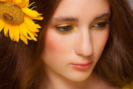Woman with stylish colorful makeup and sunflowers Stok Fotoğraf