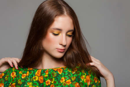 Beautiful woman with stylish green yellow makeup in dress with with floral pattern