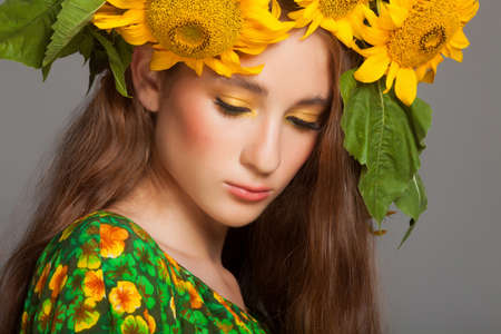 Woman with stylish makeup and sunflowers around her head