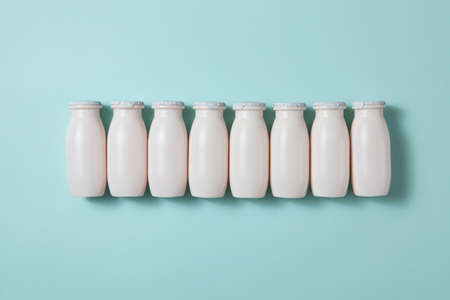 Bottles with probiotics and prebiotics dairy drink on light blue background. Bio yogurt with useful microorganisms. Production with biologically active additives. Fermentation and diet healthy food.