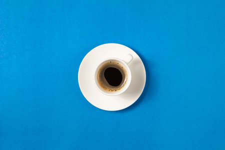 Flat lay of cup of coffee on blue background with copy space.
