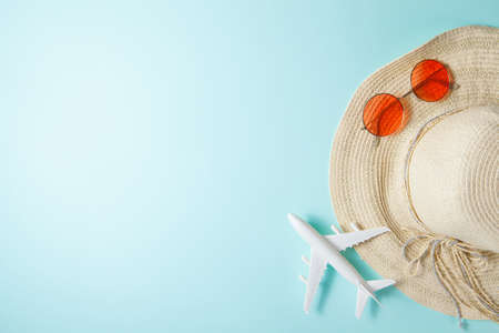 Summer 2021 vacation and travel background with sun hat, plane, sunglasses. Flat lay.