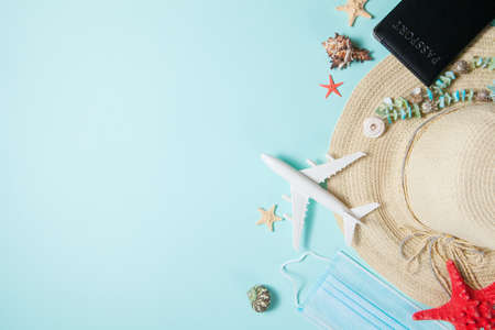 Summer 2021 vacation and travel background with sun hat, medical mask, passport, airplane and travel symbols flat lay.