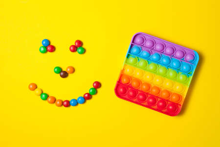 Rainbow silicone sensory antistress pop it toy with smiley from colorful candies on yellow background. Standard-Bild