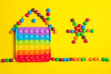 Rainbow silicone sensory antistress pop it toy with house and sun from colorful candies on yellow background.