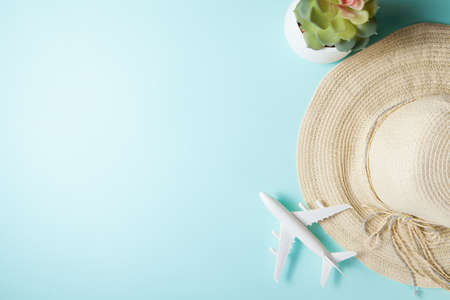 Traveling by plane. Layout on a blue background. Summer 2021 vacation and travel background with sun hat, plane, plant. Flat lay.