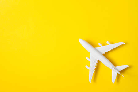 Flat lay design of travel concept with plane on yellow background with place for text. Standard-Bild