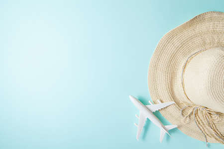 Traveling by plane. Layout on a blue background. Summer 2021 vacation and travel background with sun hat, plane. Flat lay.