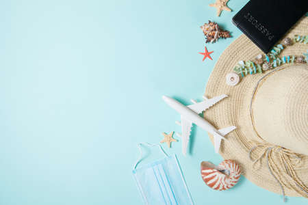 Optimistic  vacation concept. Summer 2021 vacation and travel background with sun hat, medical mask, passport, airplane and travel symbols flat lay. Waiting spring or summer time.