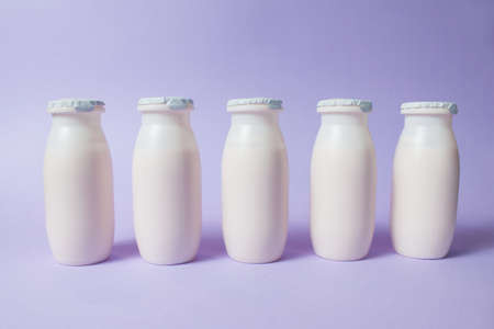 Bottles with probiotics and prebiotics dairy drink on light purple background. Bio yogurt with useful microorganisms. Production with biologically active additives. Fermentation and diet healthy food.