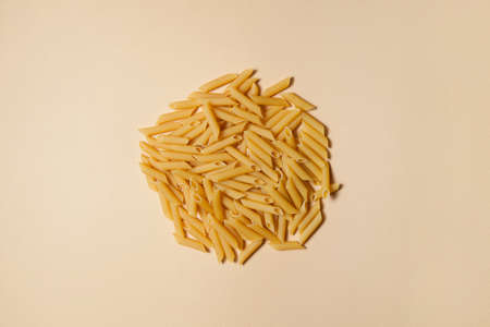 Penne pasta background. Pasta Penne texture background with space for text. Tube like macaroni. Heap of pasta.