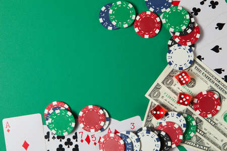 Classic playing cards, chips, red dice and dollars on green background with place for text. Gambling and casino concept. Flat lay design.