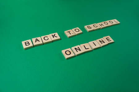 Back to School Online Text by wooden letters on a green background. Distance education due to pandemic-wide quarantine. Distance learning concept.