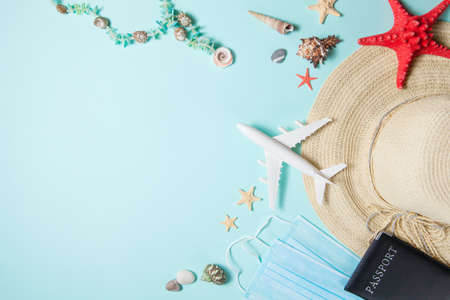 Optimistic virus vacation concept. Summer 2021 vacation and travel background with sun hat, medical mask, passport, airplane and travel symbols flat lay. Waiting spring or summer time.