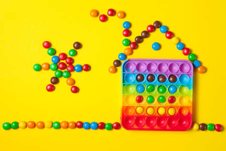 Rainbow silicone sensory toy with house and sun from colorful candies on yellow background.
