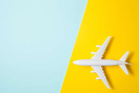 Flat lay design of travel concept with plane on yellow blue background with place for text.