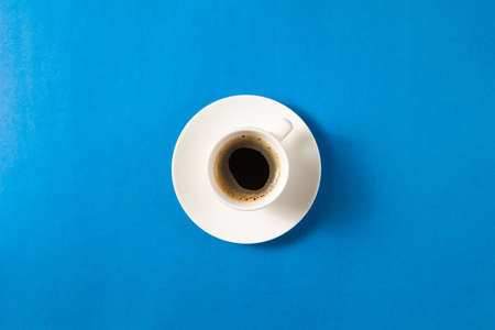 Flat lay of cup of coffee on blue background with copy space. Standard-Bild