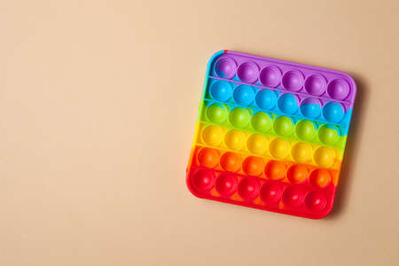 Rainbow silicone sensory antistress pop it toy on brown background. Top view. Space for text.
