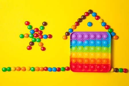 Rainbow silicone sensory antistress pop it toy with house and sun from colorful candies on yellow background. New popular trendy silicone toy.