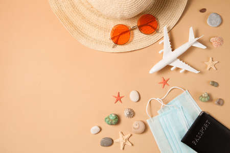 Optimistic  vacation concept. Summer 2021 vacation and travel background with sun hat, sunglasses, medical mask, passport, airplane and travel symbols flat lay. Waiting summer time. Standard-Bild