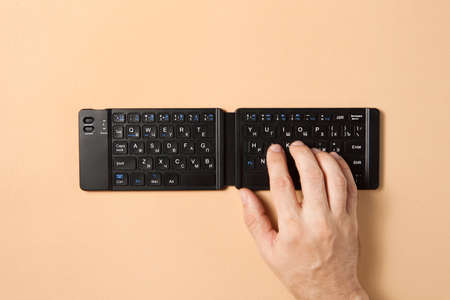 A man hand typing with wireless keyboard on the brown background. Standard-Bild