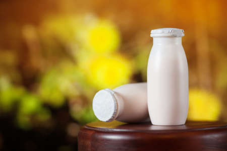 Natural liquid yogurt with probiotics in small plastic bottles on wooden table on background of green trees on a sunny day. Healthy, balanced diet food, healthy breakfast, dairy products.