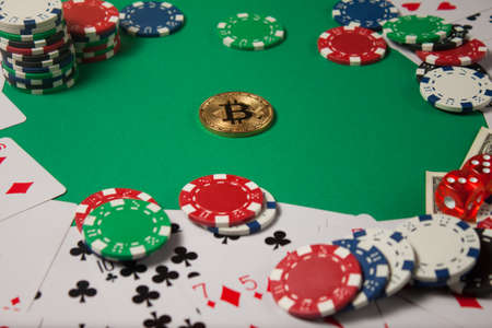 Classic playing cards, chips, red dice, bitcoin and dollars on green background. Gambling and casino concept. Standard-Bild