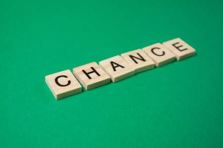 Word Chance made by wooden blocks on green background.