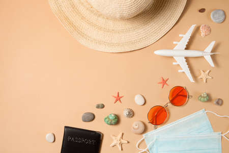 Optimistic coronavirus vacation concept. Summer 2021 vacation and travel background with sun hat, sunglasses, medical mask, passport, airplane and travel symbols flat lay. Waiting summer time.